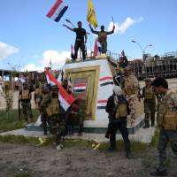 Shiite fighters from the Popular Mobilization units celebrate in front of the the provincial council building inside the northern Iraqi city of Tikrit on Tuesday during a military operation to retake it from the Islamic State group. Prime Minister Haider al-Abadi said security and allied forces backed by U.S.-led coalition aircraft have 'liberated' Tikrit. | AFP-JIJI