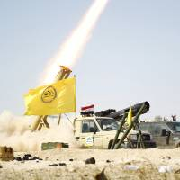 Shiite paramilitary fighters launch a rocket toward Islamic State militants in Tikrit, Iraq, Tuesday. Iraqi troops aided by Shiite paramilitaries have driven Islamic State out of central Tikrit. | REUTERS