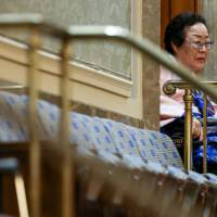 Yong Soo Lee, identified as one of the 'comfort women' forced to serve in Imperial Japanese military brothels during the war, sits in a wheel chair in the House gallery on Capitol Hill Wednesday after Prime Minister Shinzo Abe spoke before a joint meeting of Congress. | AP