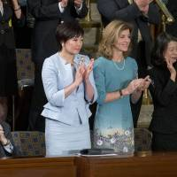 Caroline Kennedy, U.S. ambassador to Japan, and Akie Abe, wife of Prime Minister Shinzo Abe, clap as Shinzo Abe arrives to speak during a joint meeting of Congress in the House Chamber on Wednesday. Abe urged the U.S. to work closely with his country in pushing through an ambitious Asia-Pacific trade deal that he says also will promote both democracy and freedom in that region. | BLOOMBERG