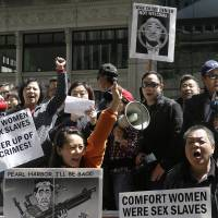 Chinese-American and Korean-American protesters hold up signs and yell as they rally Tuesday outside of the Japanese Consulate in San Francisco. Hundreds protested, calling on Prime Minister Shinzo Abe to apologize for his country's atrocities toward other parts of Asia during the war. The protest came as Abe met with President Barack Obama in Washington, D.C. | AP