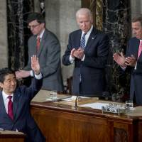 Prime Minister Shinzo Abe waves after speaking during a joint meeting of Congress with U.S. House Speaker John Boehner (right) and, U.S. Vice President Joseph 'Joe' Biden (top left) in the House Chamber at the U.S. Capitol on Wednesday. Abe urged the U.S. to work closely with his country in pushing through an ambitious Asia-Pacific trade deal that he says also will promote both democracy and freedom in that region.   BLOOMBERG