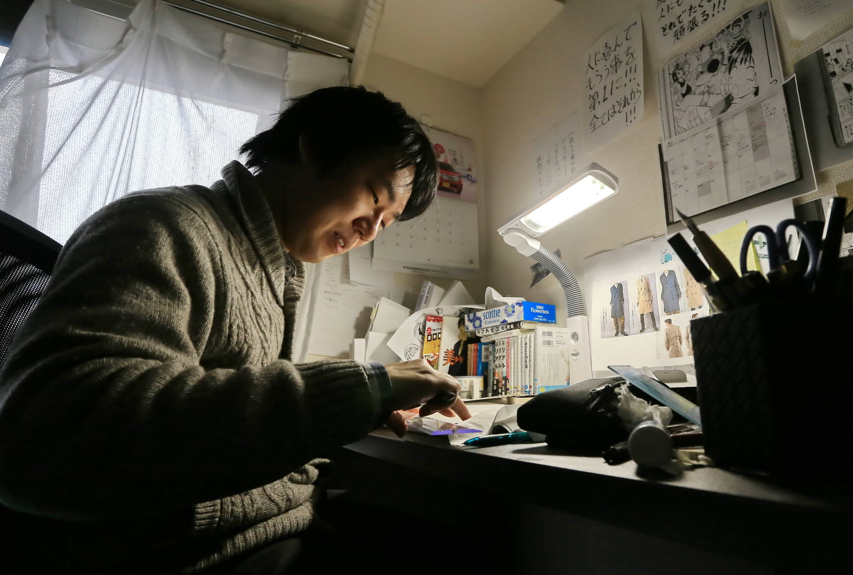 Manga writer Shoichi Tanazono works on a comic book in Nagoya that depicts his troubles with attending school as a child. | CHUNICHI SHIMBUN