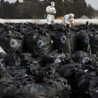 Workers work on bags containing soil, leaves and other debris from the decontamination operation in Tomioka, Fukushima Prefecture, near Tepco's Fukushima No. 2 nuclear power plant, on Feb. 24. | REUTERS