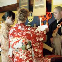 Lesbian couple Yukiko Hosomi (left) and Kaz Williams hold a wedding ceremony at Shunkoin Temple in Kyoto in December 2012. | KYODO