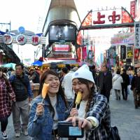 Nurses Chihiro Tanikai (left) and Mizuki Takaya take a selfie as they eat slices of pineapple on skewers in front of the entrance to the Ameyoko shopping arcade in March. | YOSHIAKI MIURA