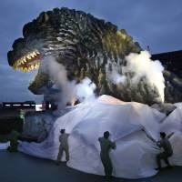 Godzilla's head, towering 52 meters high, is unveiled as the irradiated monster was appointed special resident and tourism ambassador for Tokyo's Shinjuku Ward during its awards ceremony in Tokyo on Thursday. | AP
