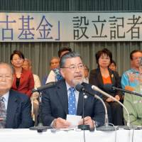 Industrialist Morimasa Goya speaks at a news conference in Naha, Okinawa Prefecture, on Thursday as Okinawa Gov. Takeshi Onaga (right) looks on. | KYODO