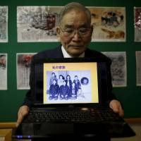 Shigeo Ito, 84, a survivor of the Hiroshima atomic bombing, displays a 1944 family photo on a laptop computer that shows his late sister, Yuki (rear, third from left), who was killed in the blast, as he demonstrates sharing with young people his experience of witnessing the horrors of the attack, at an exhibition about the 1945 atomic bombings in Higashihiroshima, Hiroshima Prefecture, on March 27. | REUTERS