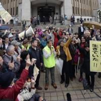 Plaintiffs who sought a provisional injunction against the restarting of the No. 3 and 4 reactors at Kansai Electric Power Co.'s Takahama nuclear power plant celebrate Tuesday outside the Fukui District Court, which ruled in their favor. | KYODO