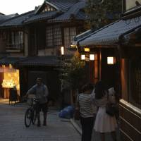 A cyclist pushes his bicycle up Ninenzaka, a famous street in Kyoto, on Oct. 7. While Japan's ancient capital is a perennial draw for foreign tourists, the city remains difficult to explore by mass transport, making bicycles a popular option for getting around. | ISTOCK