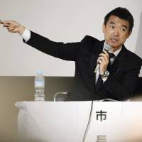 Osaka Mayor Toru Hashimoto explains his plan to consolidate the city of Osaka into five semi-autonomous wards at a town meeting with residents in Osaka on April 14, ahead of the May 17 referendum on the issue. | KYODO