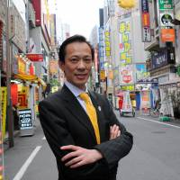 Komaki Lee, a China-born naturalized Japanese running for the Shinjuku Ward Assembly, poses in the Kabukicho entertainment district, where he made a name for himself as a tour guide. | SATOKO KAWASAKI