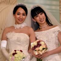 Actress Akane Sugimori (right) and partner Ayaka Ichinose, both dressed in white, pose at a press conference after a symbolic marriage ceremony in Tokyo on Sunday. The lesbian couple held the ceremony amid growing calls to legalize same-sex marriage. | AFP-JIJI