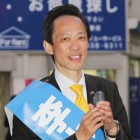 Komaki Lee, a naturalized Japanese citizen originally from China, makes a campaign speech in Tokyo's Shinjuku Ward last Thursday. Known for pioneering the nightlife tour guide business in Kabukicho, Lee failed to win a seat in the Shinjuku Ward Assembly on Sunday. | KYODO