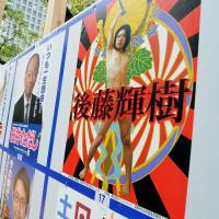 A nude poster of Teruki Goto, a candidate for the Chiyoda Ward Assembly, stands out on a campaign board in the Hibiya area of Chiyoda Ward, Tokyo, on Wednesday. | SATOKO KAWASAKI