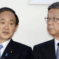 Chief Cabinet Secretary Yoshihide Suga (left) and Okinawa Gov. Takeshi Onaga attend a ceremony in the city of Ginowan on Saturday to mark the return to Japan of an area previously part of U.S. Marine Corps Camp Foster. | KYODO