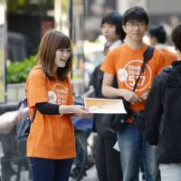 Campaigners distribute leaflets calling on residents to vote in the May 17 referendum on reorganizing the city of Osaka after campaigning kicked off Monday. | KYODO