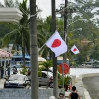 Japanese flags are displayed in Koror, Palau, on Wednesday morning ahead of the arrival of Emperor Akihito and Empress Michiko later in the day. | KYODO
