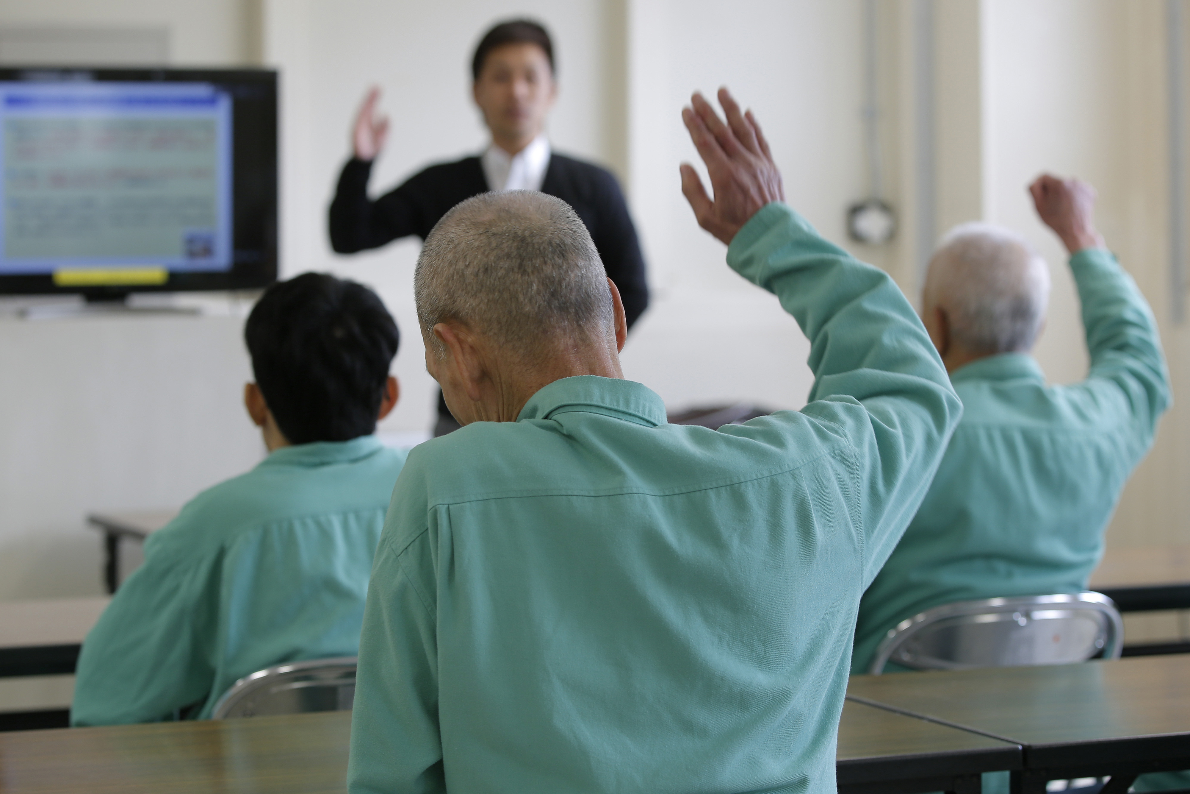 Elderly inmates raise their hands at Sasebo Prison in the city of Sasebo, Nagasaki Prefecture, on March 13. | BLOOMBERG