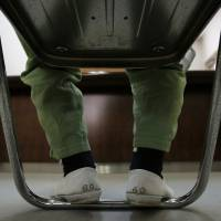 Wearing numbered shoes, an aged inmate sits in Nagasaki Prison in the city of Isahaya on March 12. | BLOOMBERG