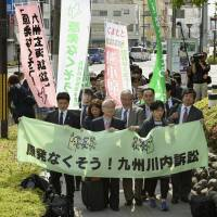 Plaintiffs, including lawyers and local residents, seeking a court decision to halt the restart of reactors at the Sendai nuclear plant, enter the Kagoshima District Court on Wednesday. | KYODO