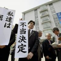 A lawyer for the plaintiffs displays a banner saying 'unjust ruling' outside the Kagoshima District Court on Wednesday. | KYODO