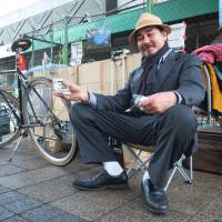 A 41-year-old homeless man who gave his name as 'Oliver' sits beside his shack in Shibuya Ward, Tokyo, on Wednesday. He holds two onigiri and nori distributed by volunteers.   ALASTAIR WANKLYN