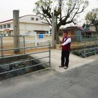 caption 1 chris 2 The father of the boy who kicked a soccer ball out of the school sports ground points to the place where a motorcycle accident occurred in Imabari, Ehime Prefecture, in March 2004. | KYODO
