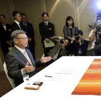 Chief Cabinet Secretary Yoshihide Suga and Okinawa Gov. Takeshi Onaga meet in a hotel in Naha on Sunday. | KYODO