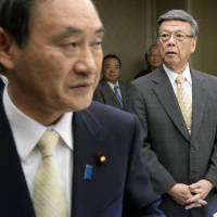 Chief Cabinet Secretary Yoshihide Suga (front) and Okinawa Gov. Takeshi Onaga head into a meeting on the U.S. base relocation issue at a hotel in Naha on Sunday. | KYODO