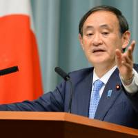 Chief Cabinet Secretary Yoshihide Suga speaks at a news conference in Tokyo on Wednesday. | KYODO