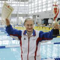 Swimmer Mieko Nagaoka, 100, smiles as she holds up a diploma and trophy after setting a world record in a 1,500-meter event held in Matsuyama, Ehime Prefecture, on Saturday. | KYODO