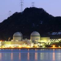 The No. 3 (left) and No. 4 reactor buildings stand at Kansai Electric Power Co.'s Takahama nuclear power station at dusk in Takahama, Fukui Prefecture, in February 2012. | BLOOMBERG