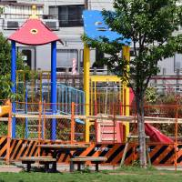 A children's climbing frame is fenced off Thursday at a park in Tokyo's Ikebukuro district after radiation of up to 480 microsieverts per hour was detected nearby. | AFP-JIJI