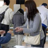 Voters cast ballots for local elections in Osaka on Sunday. Governors, mayors and local assembly members across Japan will be chosen by voters in the first of two rounds of unified quadrennial local elections. | KYODO