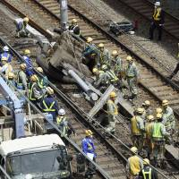 Workers try to clear away a pole that collapsed on the train tracks between Kanda Station and Akihabara Station on the JR Yamanote Line on Sunday morning. | KYODO