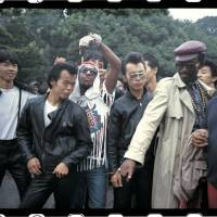 Rockers and rappers: Busy Bee and Fab 5 Freddy from 'Wild Style' mingle with rockers in Tokyo's Yoyogi Park after overcoming initial concerns the leather-clad group were gang members. | CHARLIE AHEARN