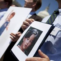 Fathers who lost their children to spousal abduction to Japan hold photos of their kids in Washington in May 2010.  | AP