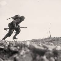 Invasion: A U.S. soldier crosses open ground under fire in Okinawa on May 10, 1945. | WIKIMEDIA COMMONS/NATIONAL ARCHIVES AND RECORD