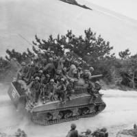 Highway to hell: Troops travel on a tank to the town of Ghuta, Okinawa, on April 1, 1945. | WIKIMEDIA COMMONS/NATIONAL ARCHIVES AND RECORD