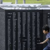 Young one: A boy runs by the Cornerstone of Peace monument at the Peace Memorial Park in Itoman on the island of Okinawa in March. | AP