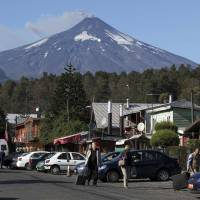 Under the mountain: Smoke and ash rise from Villarrica volcano above Pucon town, located south of Santiago. | REUTERS