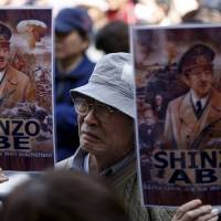 Call of dissent: People hold placards depicting Prime Minister Shinzo Abe as German dictator Adolf Hitler at a protest in Tokyo last month.   REUTERS