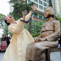 Show of emotion: A woman takes part in a protest about 'comfort women' outside of the Japanese Embassy in Seoul in 2012. A similar statue to the one above now sits in a park in Glendale, California. | KYODO