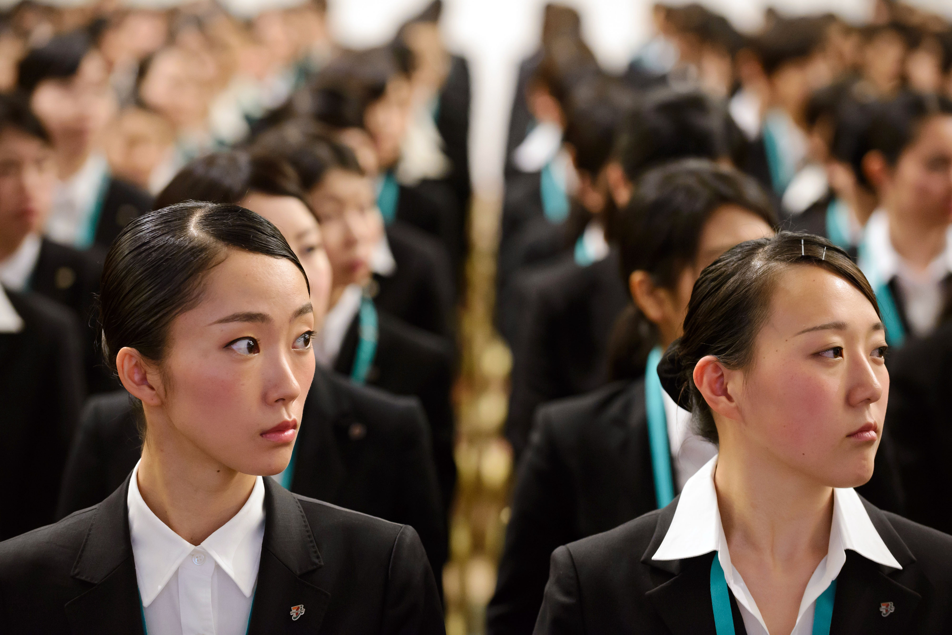 Not a chapatsu in the place: New recruits for Seven & I Holdings Co. attend an initiation ceremony in Tokyo, with nary a lighter-hued hair in sight. April marks the start of many young people's working lives in Japan. | AKIO KON / BLOOMBERG