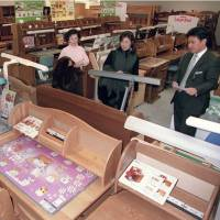Out of touch: An assistant shows customers around an Otsuka Kagu store in Tokyo in 2002. Falling sales suggest that the furniture retailer's business model — which involved sales staff guiding 'members' through stores full of mostly domestically made goods — no longer appeals to Japanese customers, who now have a more idiosyncratic and casual approach to buying furniture. | KYODO