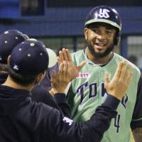 He's back: The Swallows' Wladimir Balentien is greeted by teammates after scoring a run in the second inning on Friday against the Yomiuri Giants at Jingu Stadium. Balentien helped Tokyo Yakult defeat Yomiuri 3-2 in 10 innings. | KYODO