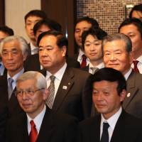 A step forward: Japan 2024 Task Force co-chair Saburo Kawabuchi (center) poses for a photo along with the representatives of the club that submitted applications to join Japan's new men's pro basketball league for the 2016-17 season on Friday in Tokyo. | KAZ NAGATSUKA