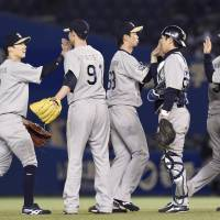 Long road back: Buffaloes players celebrate on the mound after their 12-inning win over the Marines on Tuesday. | KYODO